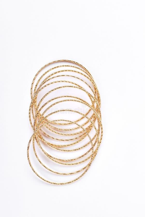 Colección de pulseras de oro en el fondo blanco foto de archivo libre de regalías