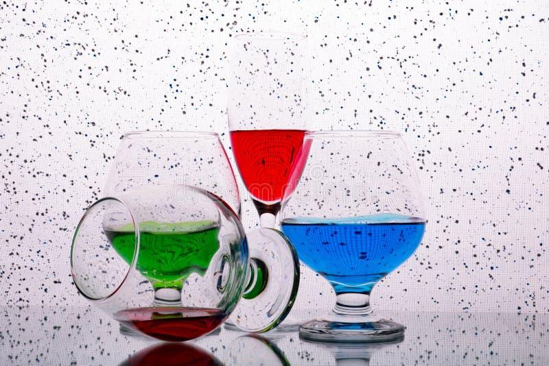 Colección de vidrios con las bebidas coloreadas imagenes de archivo