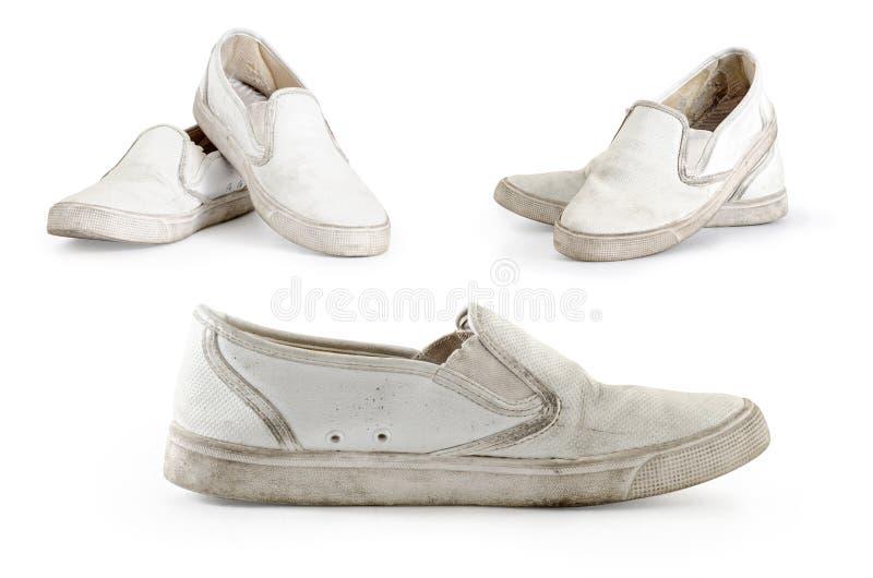 Colección de zapatillas de deporte sucias viejas en un fondo blanco imagenes de archivo