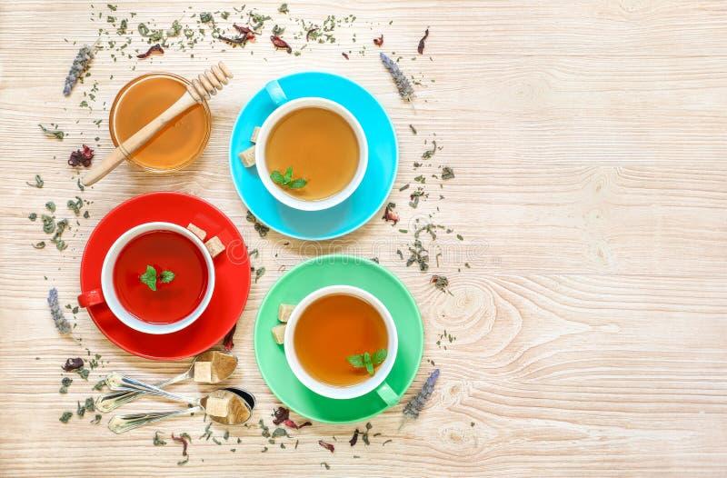 Colección del té de tres diversos tipos del té - menta, hibisco y infusión de hierbas en tazas en el fondo de madera foto de archivo