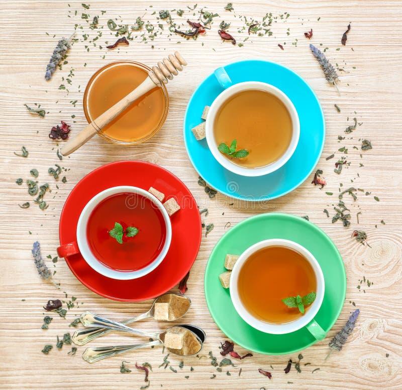 Colección del té de tres diversos tipos del té - menta, hibisco y infusión de hierbas en tazas en el fondo de madera imágenes de archivo libres de regalías