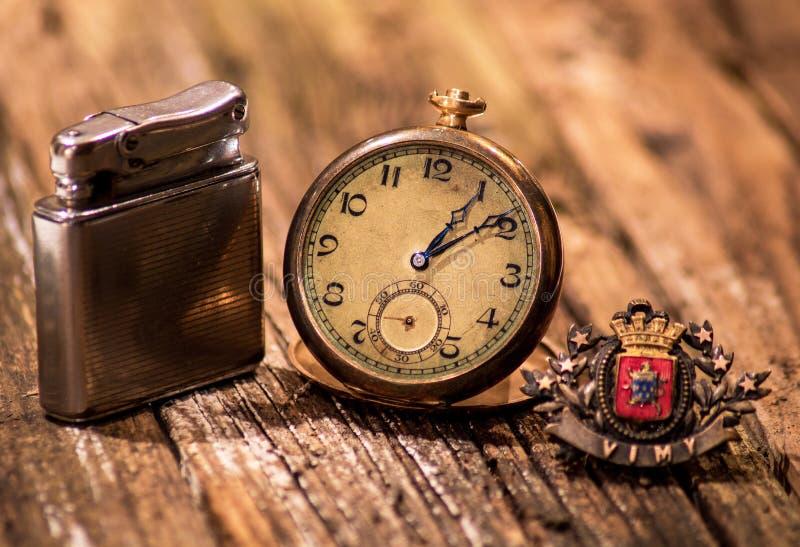 Colección del tiempo de guerra del vintage: Encendedor, reloj de bolsillo, Pin foto de archivo libre de regalías