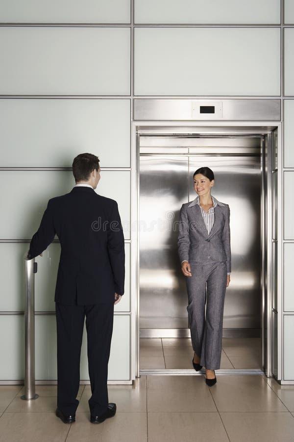 Colega de Looking At Female del hombre de negocios que sale el elevador imágenes de archivo libres de regalías