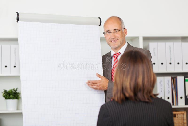 Colega de trabalho da fêmea de Giving Presentation To do homem de negócios fotos de stock