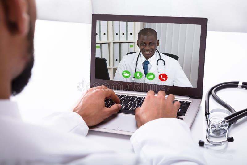 Colega del doctor Video Conferencing With en el ordenador portátil imagenes de archivo