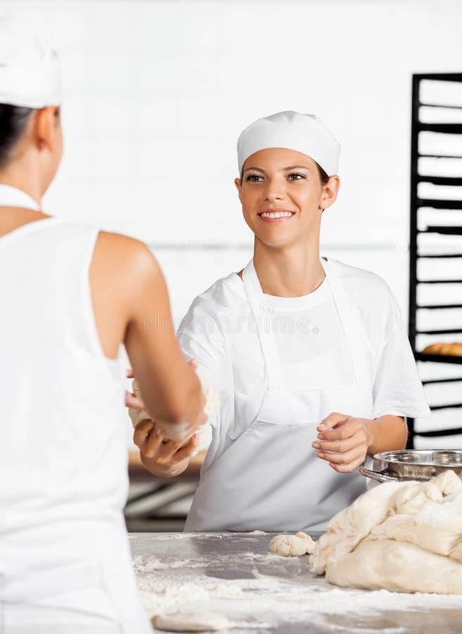 Colega fêmea de Giving Dough To do padeiro fotografia de stock royalty free