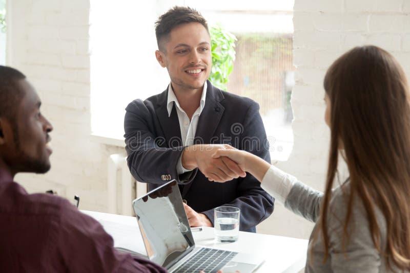 Colega fêmea do aperto de mão masculino do trabalhador na instrução da empresa fotografia de stock