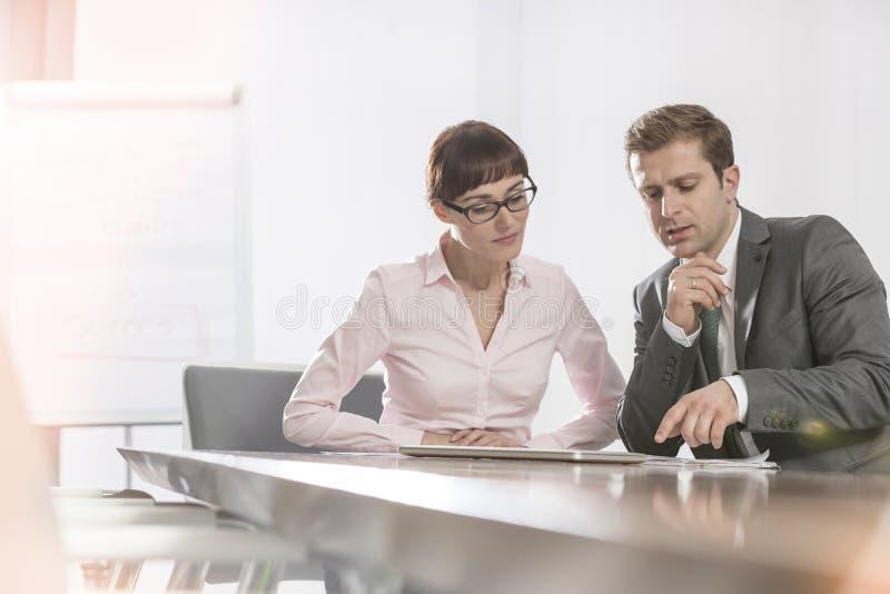 Colegas adultos meados de do negócio que discutem ao sentar-se na tabela de conferência na sala de reuniões imagens de stock royalty free