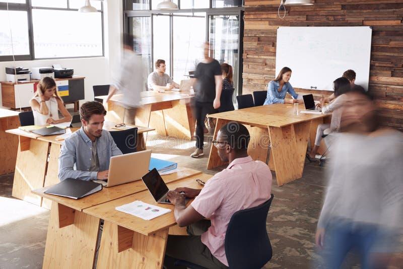 Colegas adultos novos que trabalham em um escritório ocupado, borrão de movimento imagens de stock royalty free