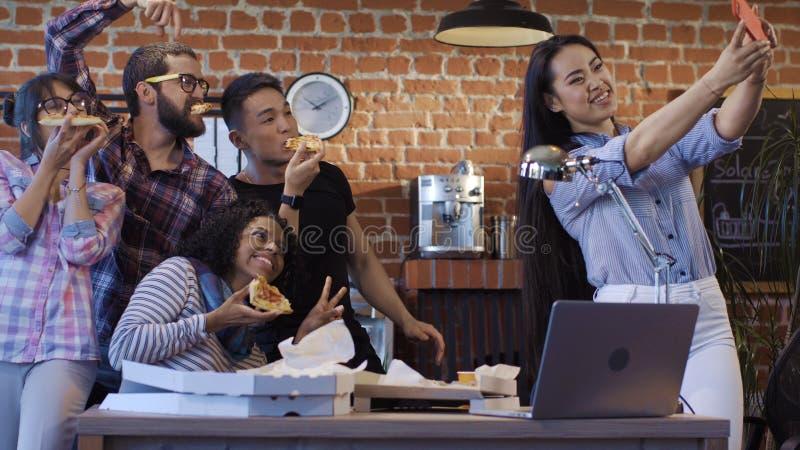 Colegas alegres que tomam o selfie com pizza fotografia de stock royalty free