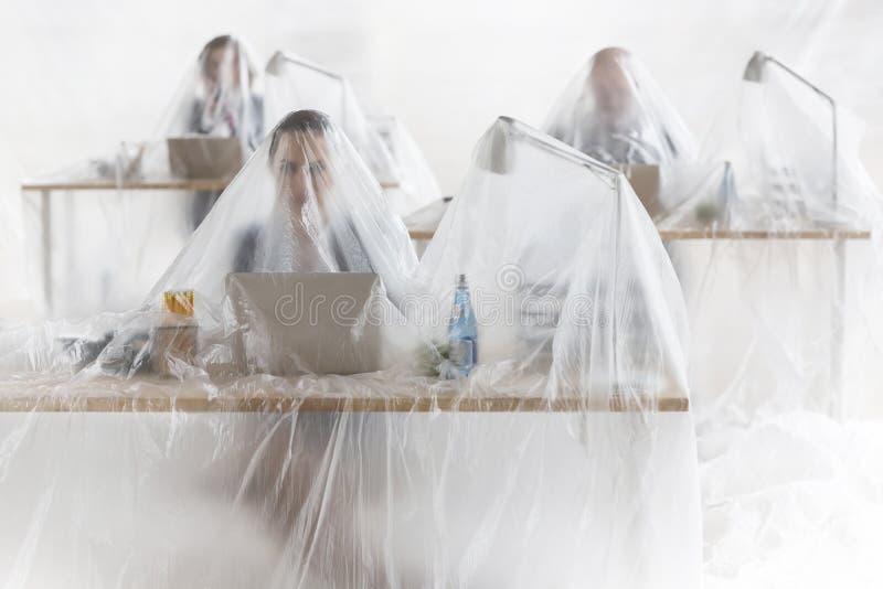 Colegas atrapados del negocio que usan los ordenadores portátiles en los escritorios cubiertos en plástico imagenes de archivo