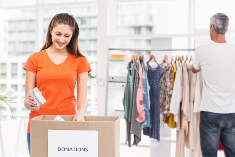 Colegas casuales del negocio que clasifican donaciones foto de archivo libre de regalías