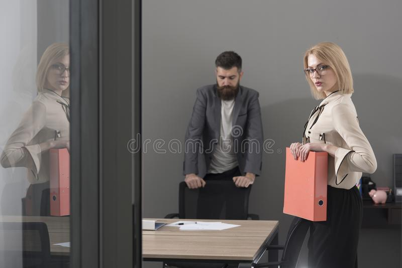 Colegas confiados y acertados en el trabajo Papeleo antes del trato Mujer y hombre barbudo en fondo de la oficina Negocios fotos de archivo libres de regalías