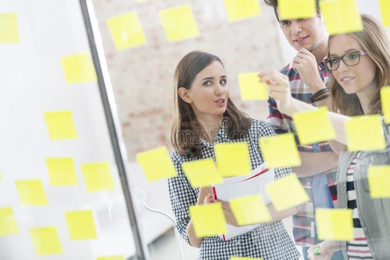 Colegas creativos del negocio que planean estrategias en notas adhesivas imagenes de archivo