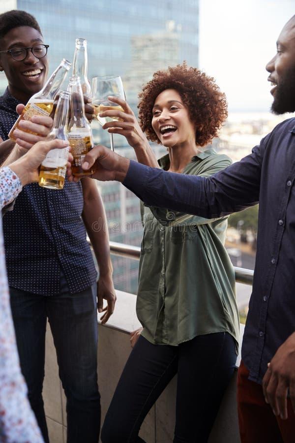 Colegas criativos de sorriso do negócio que bebem após o trabalho que aumenta vidros para fazer um brinde, vertical foto de stock