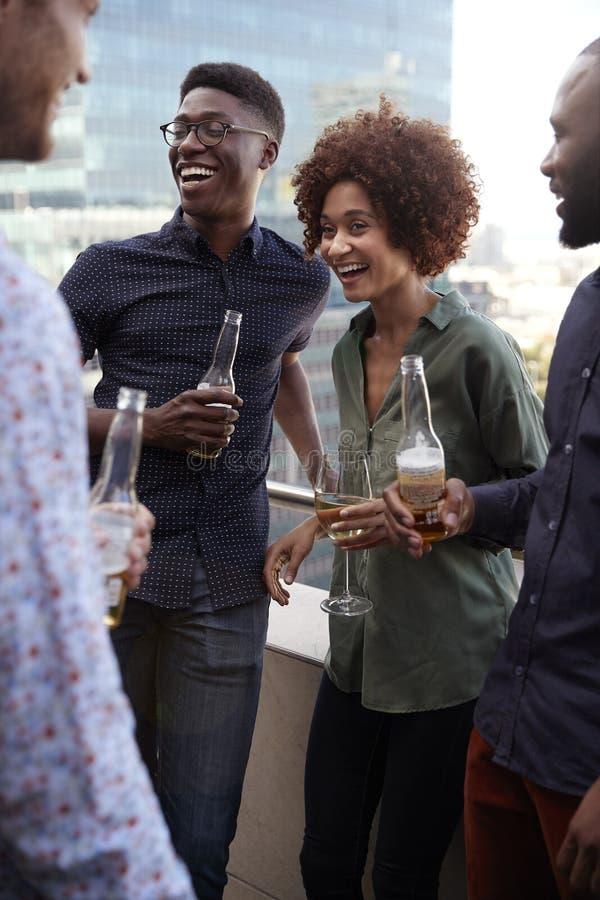 Colegas criativos de sorriso do negócio que socializam com bebidas após o trabalho, vertical fotos de stock