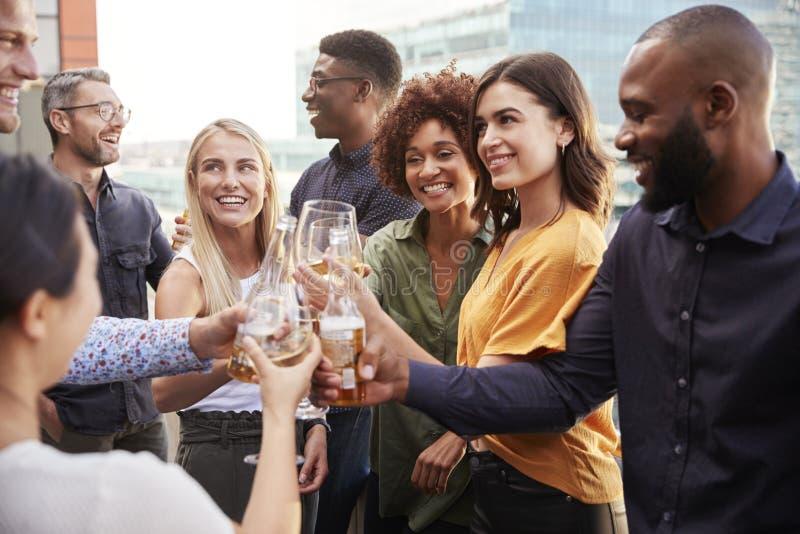 Colegas criativos do negócio que aumentam vidros e que fazem um brinde com bebidas após o trabalho fotografia de stock