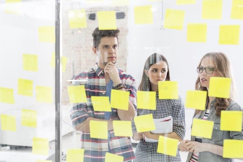 Colegas criativos do negócio que discutem sobre estratégias em notas adesivas fotografia de stock royalty free