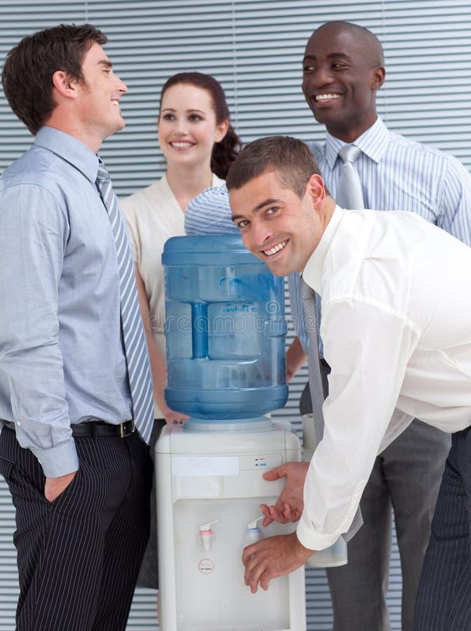 Colegas de Busines que falam em torno do refrigerador de água fotografia de stock royalty free