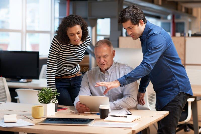 Colegas de escritório que falam o negócio junto sobre uma tabuleta digital foto de stock royalty free