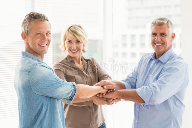 Colegas de sorriso do negócio que empilham as mãos fotografia de stock