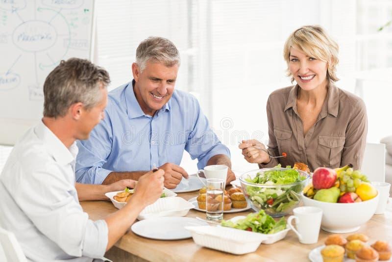 Colegas de sorriso do negócio que têm o almoço junto fotos de stock royalty free