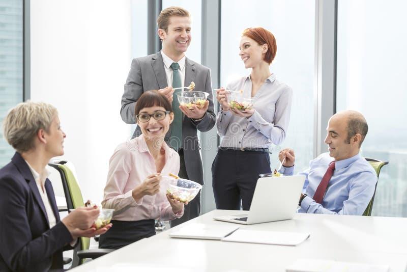 Colegas de sorriso do neg?cio que comem o almo?o na sala de reuni?es durante o encontro no escrit?rio fotos de stock