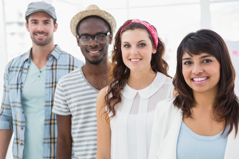 Colegas de sorriso que estão e que levantam em uma linha fotos de stock royalty free