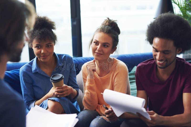 Colegas de trabalho adultos novos que têm a reunião de negócios imagens de stock royalty free