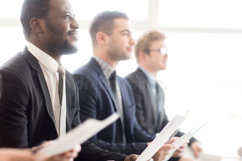 Colegas de trabalho atentos que escutam o discurso na reunião foto de stock