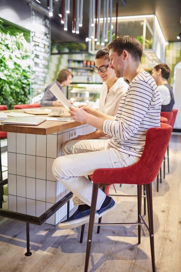 Colegas de trabalho com os papéis que sentam-se na tabela imagens de stock