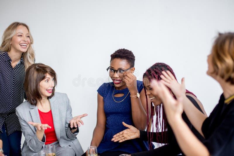 Colegas de trabalho das fêmeas que comemoram a partida bem sucedida de um projeto novo imagens de stock royalty free