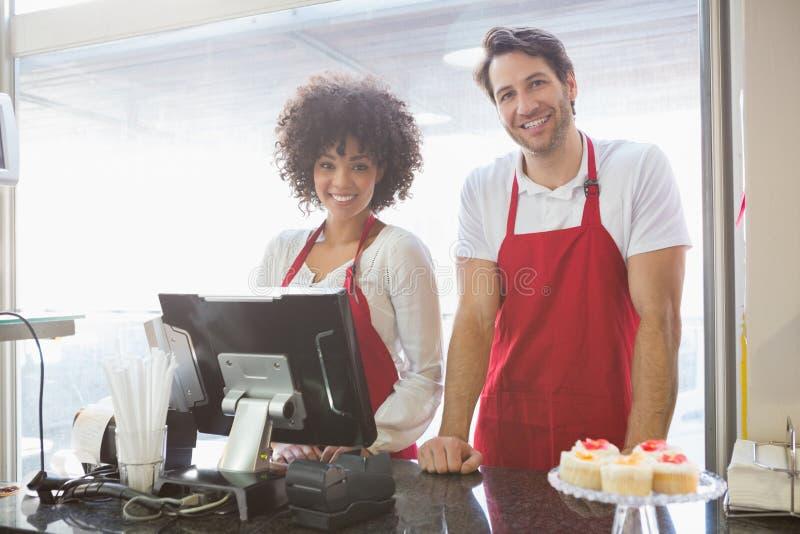 Colegas de trabalho de sorriso que levantam junto atrás do contador foto de stock royalty free