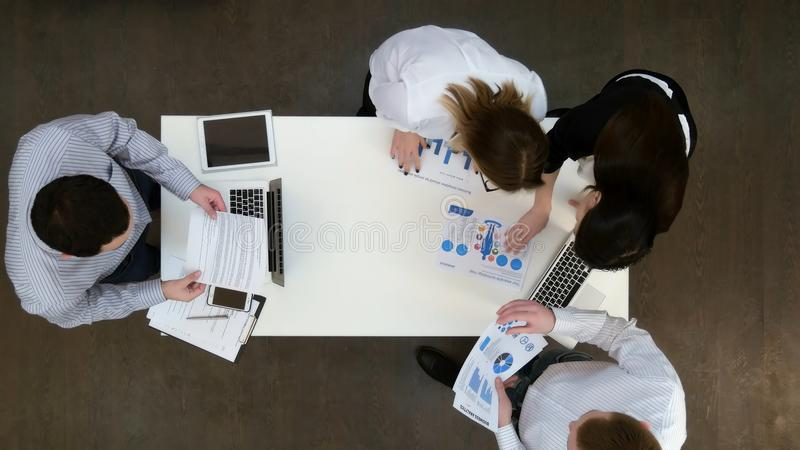 Colegas de trabalho do escritório com portáteis e relatórios que recolhem para a reunião de negócios imagem de stock