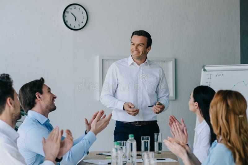 colegas de trabalho do negócio que aplaudem ao mentor de sorriso ao ter o treinamento do negócio foto de stock royalty free