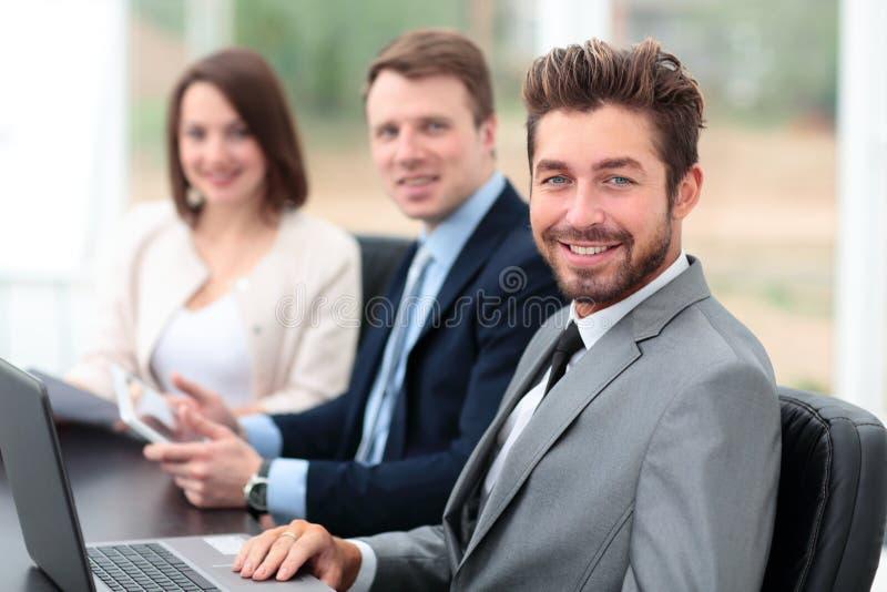 Colegas de trabalho elegantes que olham a câmera durante a reunião no escritório fotos de stock royalty free