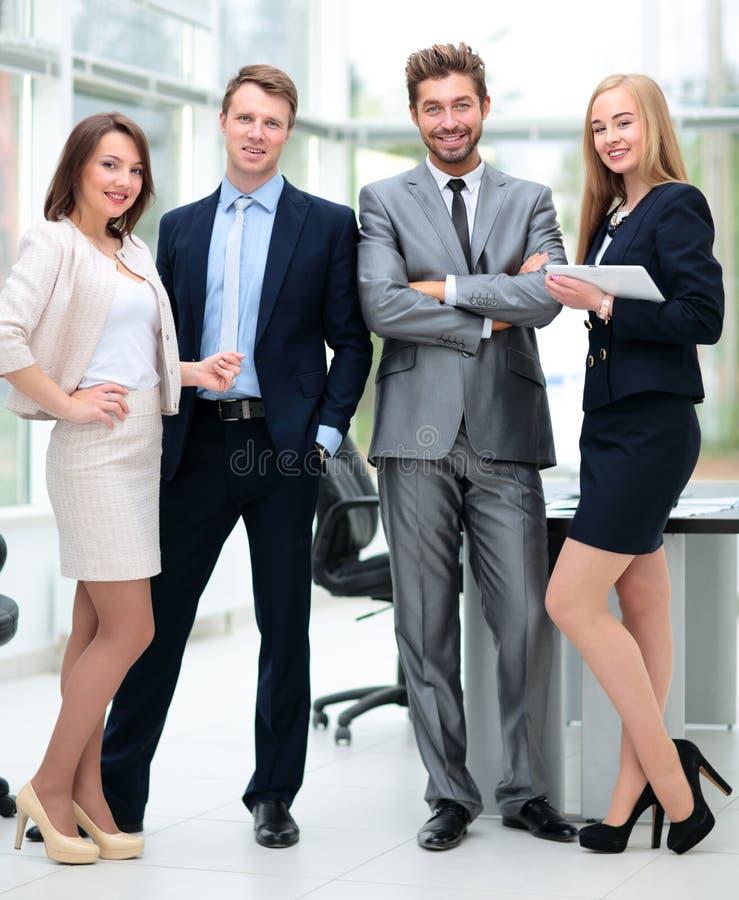 Colegas de trabalho elegantes que olham a câmera durante a reunião no escritório imagens de stock royalty free