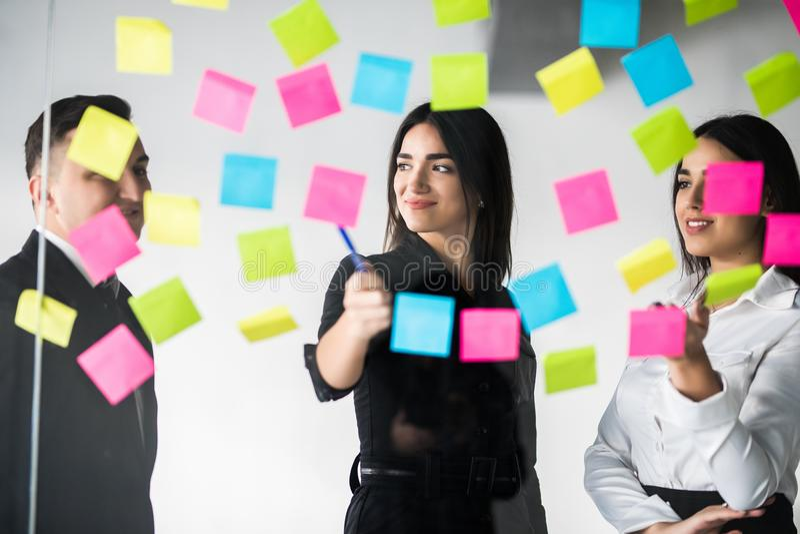 Colegas de trabalho masculinos e fêmeas novos que escrevem notas restantes para os colegas que planeiam o processo do funcionamen fotos de stock