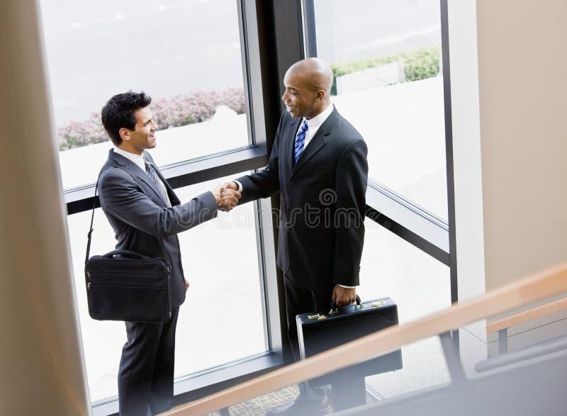 Colegas de trabalho masculinos que agitam as mãos no canto do escritório imagem de stock royalty free