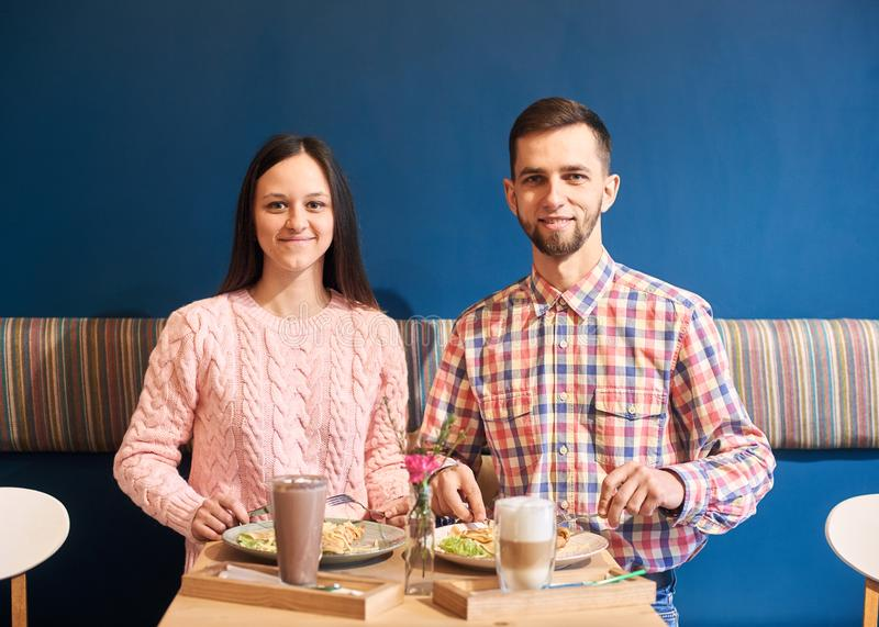Colegas de trabalho novos dos amigos dos pares que têm o almoço no café atmosférico Parede decorada azul no fundo Tiro do retrato foto de stock royalty free