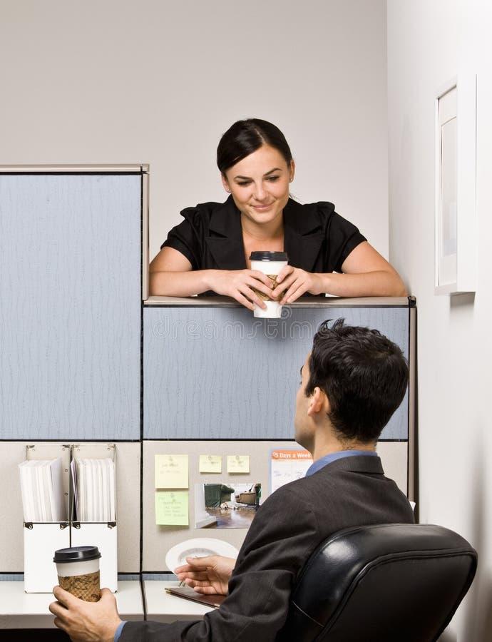 Colegas de trabalho que falam no compartimento do escritório fotografia de stock