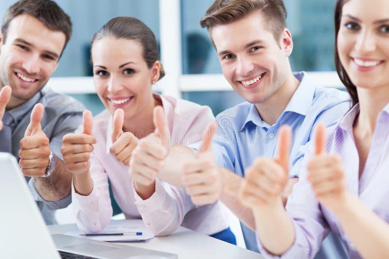 Colegas de trabalho que mostram os polegares acima imagem de stock royalty free
