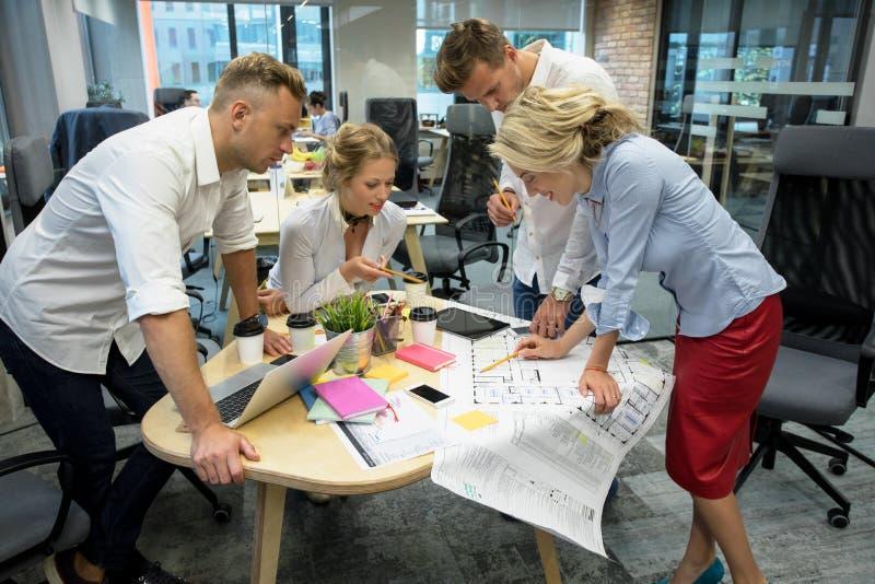 Colegas de trabalho que trabalham no grupo no projeto imagem de stock royalty free