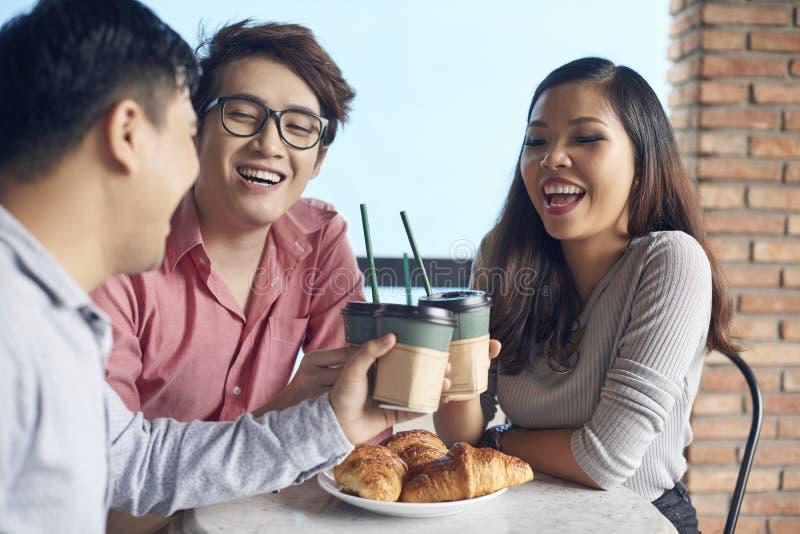 Colegas de trabalho de riso contemporâneos que comem o café fotografia de stock royalty free