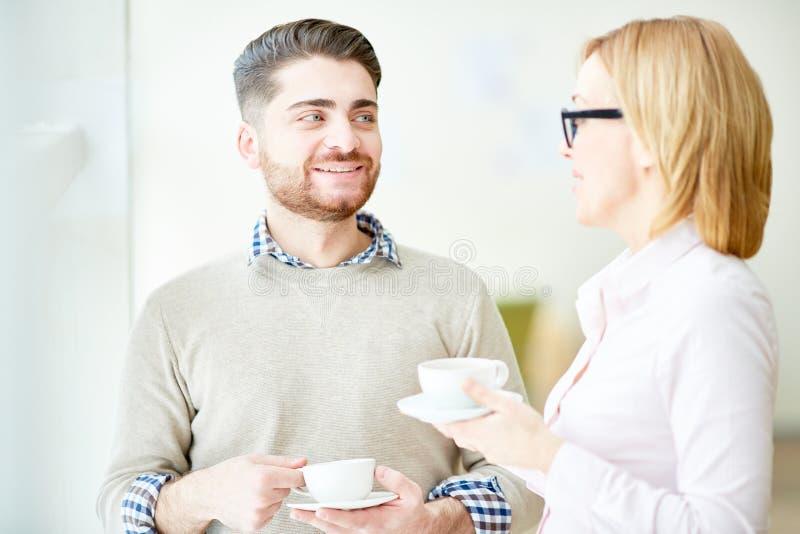 Colegas de trabalho satisfeitos que apreciam o café imagens de stock