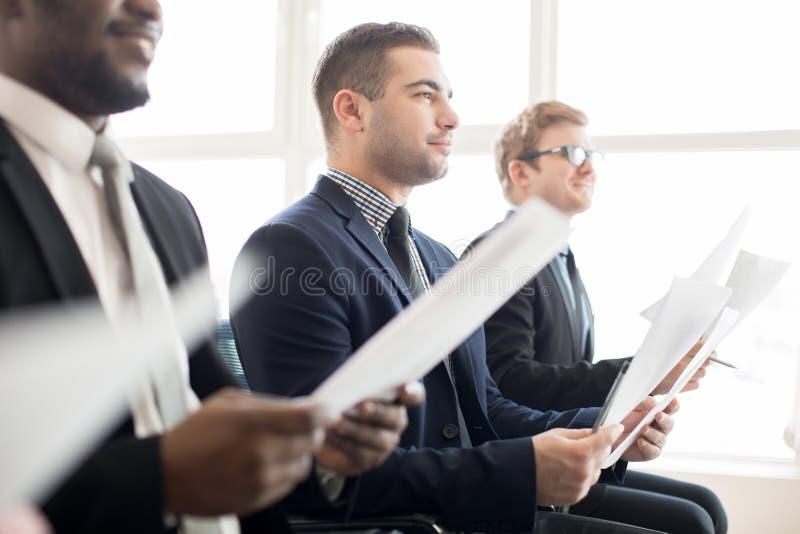 Colegas de trabalho satisfeitos que escutam a apresentação foto de stock