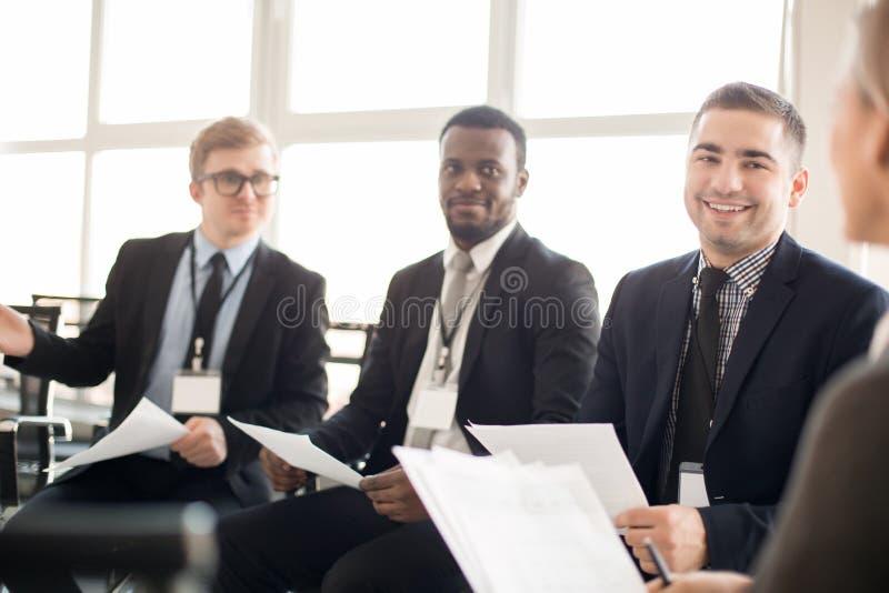 Colegas de trabalho de sorriso que têm a reunião amigável imagens de stock royalty free