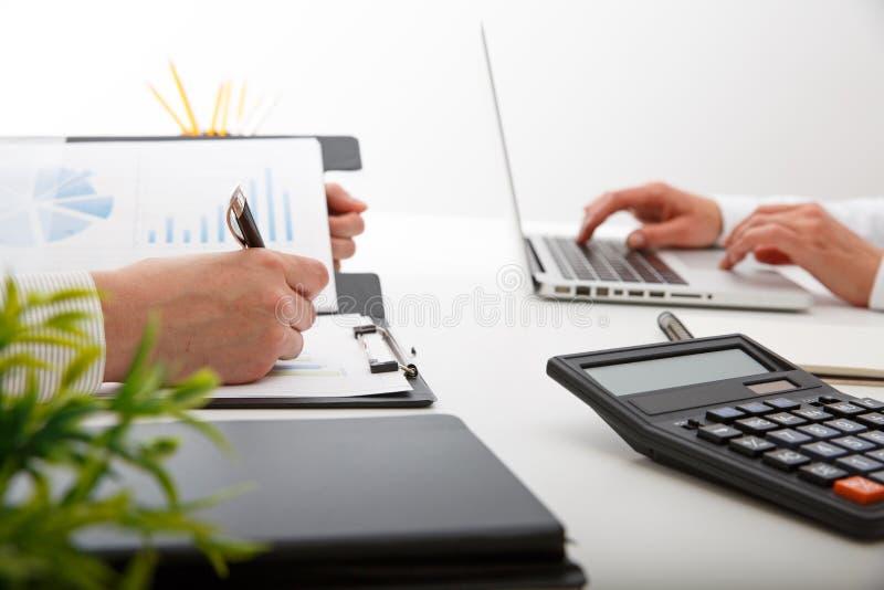 Colegas del equipo dos del negocio que discuten datos financieros del gráfico del nuevo plan sobre la tabla de la oficina fotos de archivo
