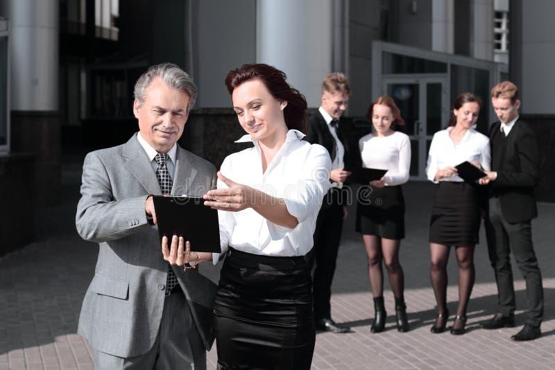 Colegas del negocio con los documentos que se colocan delante del edificio de oficinas imagen de archivo libre de regalías