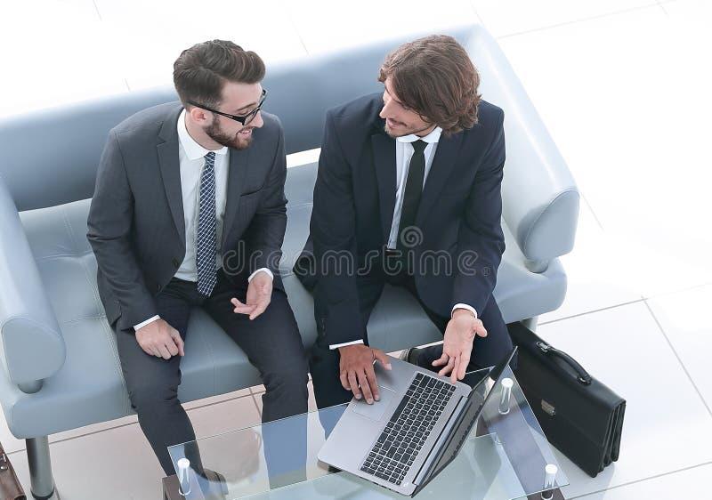 Colegas del negocio que discuten datos del ordenador port?til imágenes de archivo libres de regalías